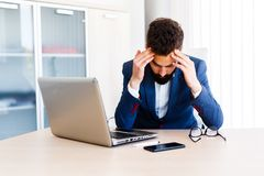 Young Handsome Businessman Has Headache. Young Business Man Working On Laptop At Office - Workplace Stock Photo