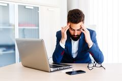 Young Handsome Businessman Has Headache. Young Sleepy Business Man Sitting At Workplace - In office Royalty Free Stock Image
