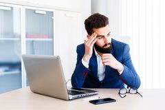 Young Handsome Businessman Has Headache. Young Sleepy Business Man Sitting At Workplace - In office Royalty Free Stock Photo