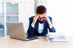 Young Handsome Businessman Has Headache. Young Sleepy Business Man Sitting At Workplace - In office Royalty Free Stock Photography