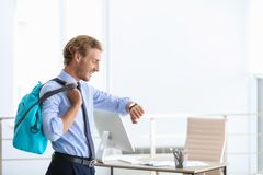 Young handsome businessman holding fitness bag. In office. Space for text stock photography