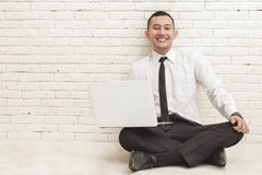 Young handsome businessman with laptop smiling and sitting on th Stock Images
