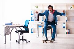 The young handsome businessman with longboard in the office. Young handsome businessman with longboard in the office royalty free stock image