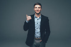 Young handsome businessman pointing with finger on back on grey Royalty Free Stock Photo