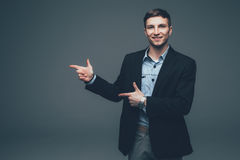 Young handsome businessman pointing with finger on side on grey Stock Image