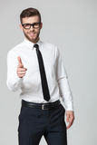 Young handsome businessman pointing at you  isolated on gray bac Stock Images