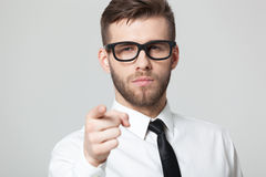 Young handsome businessman pointing at you  isolated on gray bac Royalty Free Stock Photography