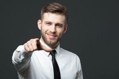 Young handsome businessman pointing at you  isolated on gray bac Stock Image