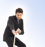 A young and handsome businessman pulling a rope Royalty Free Stock Image