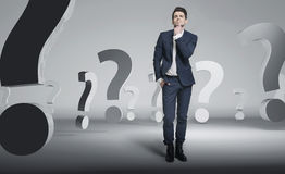 Young handsome businessman among question marks Royalty Free Stock Images