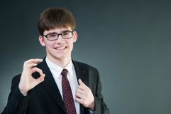Young handsome businessman showing ok sign. Isolated on black background Stock Photo