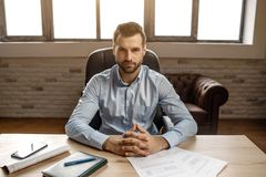 Free Young Handsome Businessman Sit At Table And Pose In His Own Office. He Look Straight On Camera. Notebook Journal And Stock Images - 140700814