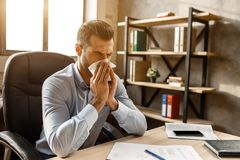 Young handsome businessman sit at table and sneeze in his own office. He cover nose with white napkin. Sick guy suffer. Young handsome businessman sit at table royalty free stock image