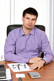 Young handsome businessman sitting at his desk royalty free stock photos