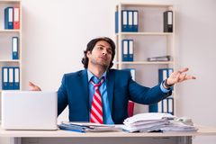 The young handsome businessman sitting in the office. Young handsome businessman sitting in the office royalty free stock image
