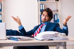The young handsome businessman sitting in the office. Young handsome businessman sitting in the office royalty free stock photography