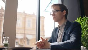 Young handsome businessman is sitting at table in cafe, looking forward, talking, guy in glasses is listening to stock video