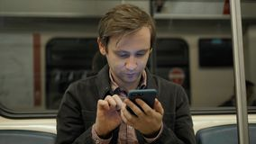 Young handsome businessman with smartphone in subway, man student in underground railway station trasportation public. Young handsome businessman with smartphone stock video footage