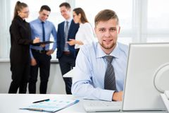 Businessman working in an office. Young handsome businessman smiling at camera when using computer in the office Royalty Free Stock Photos