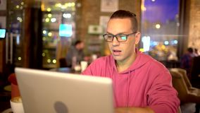 Young handsome businessman student, at the table working with a laptop, wearing glasses, smiling. Concept: new stock video