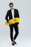 Young handsome businessman in suit and suglasses holding yellow skateboard. Full length portrait of a young handsome businessman in suit and suglasses holding Royalty Free Stock Photography