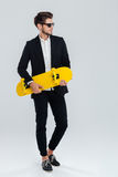 Young handsome businessman in suit and suglasses holding yellow skateboard. Over gray background Royalty Free Stock Photos