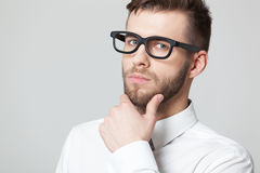 Young handsome businessman thinking on gray background. Stock Photography