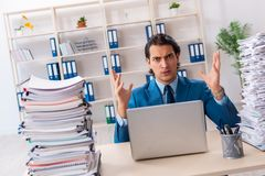 The young handsome businessman unhappy with excessive work. Young handsome businessman unhappy with excessive work royalty free stock photos