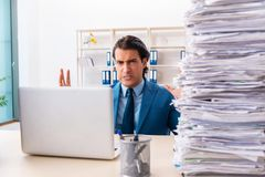 The young handsome businessman unhappy with excessive work. Young handsome businessman unhappy with excessive work royalty free stock photography