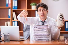 The young handsome businessman unhappy with excessive work. Young handsome businessman unhappy with excessive work stock image