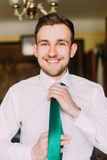 Young handsome businessman in white shirt dressing green tie with happy smile on his face Stock Photos