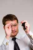 Young handsome businessman wiping eyeglasses Stock Photo
