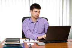 Young handsome businessman working on laptop stock image