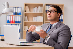 The young handsome businessman working on office. Young handsome businessman working on office Stock Image