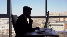 Young handsome businessman is working, sitting at table, talking on phone on background of window in modern office, side stock video