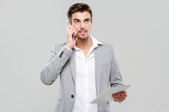 Young handsome businessman working using cellphone and tablet Stock Photo