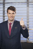 Young handsome businessmen showing thumb-up in the office stock photography