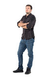 Young handsome casual man in jeans and shirt with crossed arms looking up. Stock Photo