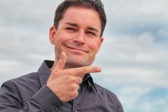 Young handsome casual man pointing by right hand finger with white smiling face Stock Images