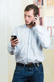 Young handsome casual man using two cell phones Stock Images