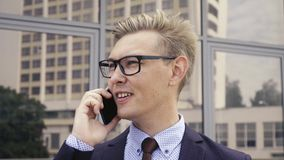 Young handsome Caucasian businessman in glasses talking on mobile phone in front of office building. Male executive. Young handsome Caucasian businessman in stock footage