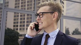 Young handsome Caucasian businessman in glasses talking on mobile phone in front of office building. Male executive. Young handsome Caucasian businessman in stock video footage