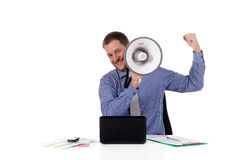 Young handsome caucasian businessman, success. Young handsome caucasian businessman with a megaphone in front face, clench fist as success symbol. Studio shot Royalty Free Stock Photography