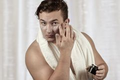 Young handsome caucasian man applying cream under the eyes, towel on shoulders. Caring face, metrosexual daily routine in the bath stock photo