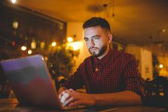 A young handsome Caucasian man with beard and toothy smile in a red checkered shirt is working behind a gray laptop Royalty Free Stock Photos