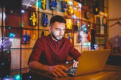 A young handsome Caucasian man with beard and toothy smile in a red checkered shirt is working behind a gray laptop. Sitting at a wooden table. Hands on the Royalty Free Stock Image