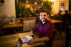 A young handsome Caucasian man with beard and toothy smile in red checkered shirt is working behind laptop sitting at wooden table Royalty Free Stock Photography