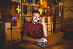 Young handsome Caucasian man with beard and toothy smile in red shirt works behind laptop, hands on keyboard sitting at wooden tab Stock Images