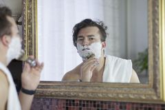 Young handsome caucasian man begins to shave with brush and foam, vintage style of old barber. Thoughtful serious look,. Young handsome caucasian man begins to stock photography