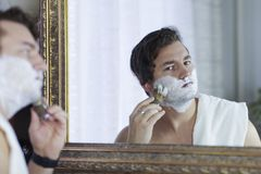 Young handsome caucasian man begins to shave with brush and foam, vintage style of old barber. Thoughtful serious look. Young handsome caucasian man begins to stock image